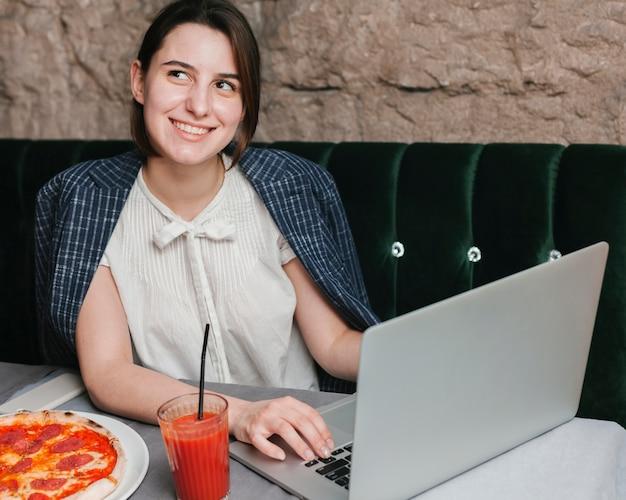 Jovem feliz usando laptop Foto gratuita