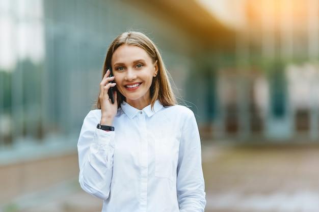 Jovem fêmea chamando em um telefone. mulher de negócios atraente falando por telefone. . internet tecnologia e conceito de pessoas felizes. Foto Premium