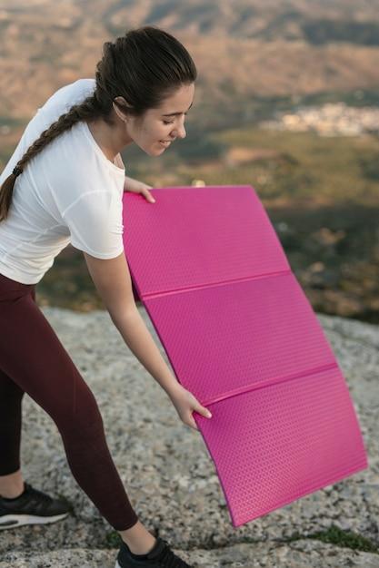 Jovem fêmea colocando tapete de ioga na montanha Foto gratuita