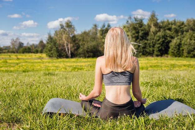 Jovem fêmea com braços abertos e longos cabelos loiros, sentado e relaxa em pose de ioga na natureza verde Foto Premium