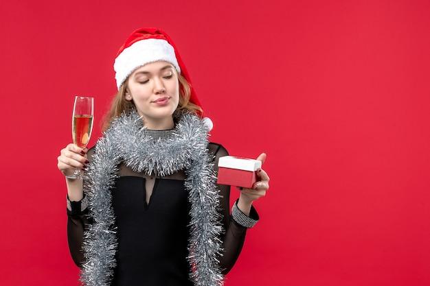 Jovem fêmea com presente comemorando na cor vermelha feriados natal Foto gratuita
