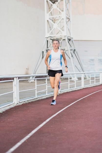 Jovem fêmea correndo no estádio Foto gratuita