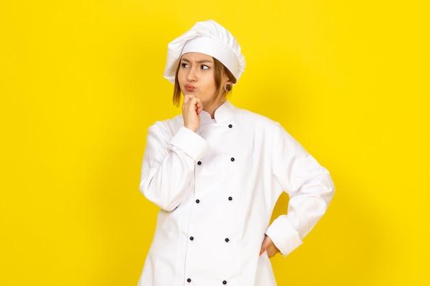 Jovem fêmea cozinhando no fato de cozinheiro branco e expressão de pensamento de boné branco Foto gratuita