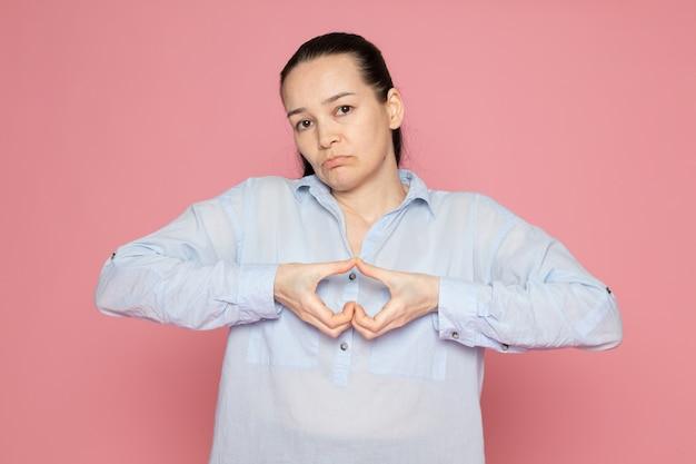 Jovem fêmea de camisa azul, posando na parede rosa Foto gratuita