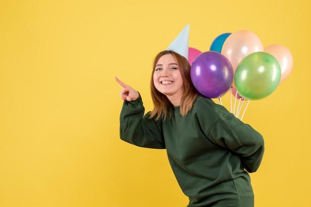 Jovem fêmea escondendo balões coloridos de frente Foto gratuita