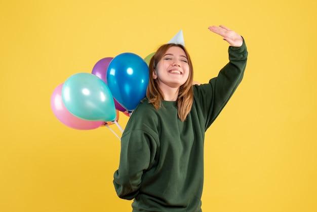 Jovem fêmea escondendo balões coloridos nas costas Foto gratuita