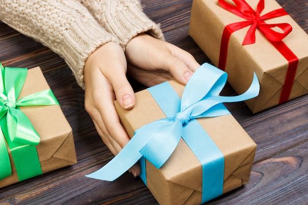 Jovem fêmea mãos segurando presentes com fita colorida Foto Premium