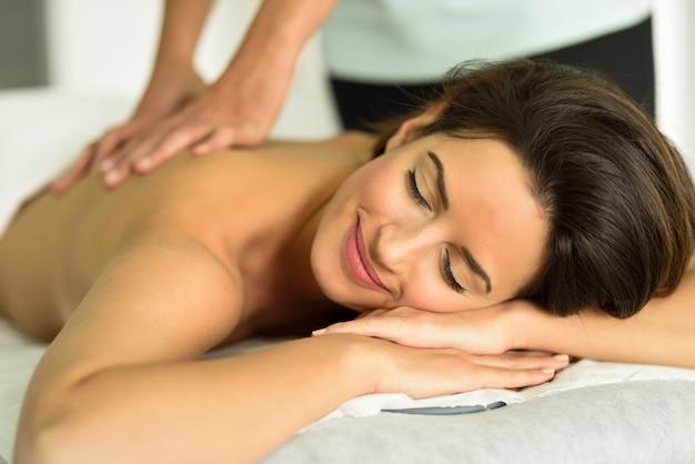 Jovem fêmea que recebe uma relaxante massagem nas costas em um centro de spa. Foto gratuita