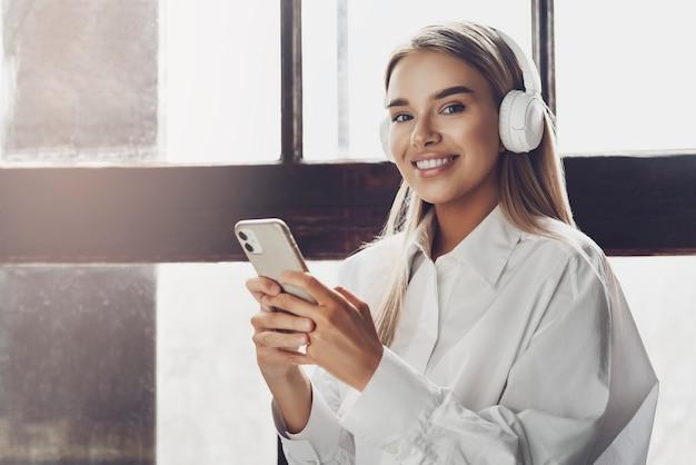 Jovem fêmea segurando o smartphone nas mãos, ouvindo música em fones de ouvido. Foto Premium