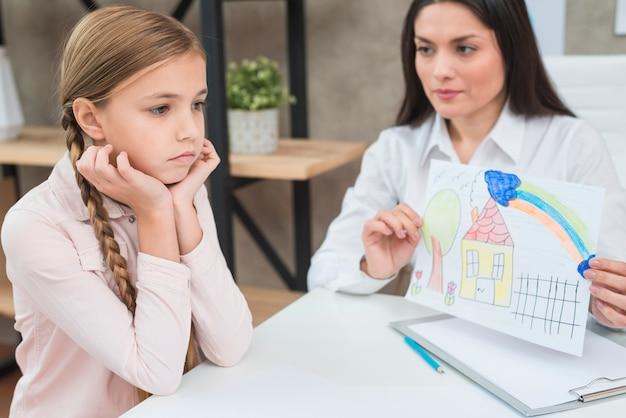 Jovem, femininas, psicólogo, mostrando, papel desenho, com, casa tirada, para, triste, sério, menina Foto gratuita