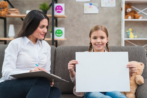 Jovem, femininas, psicólogo, olhar, menininha, mostrando, em branco, livro branco, para, câmera Foto gratuita