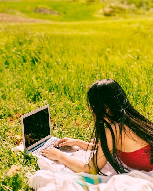 Jovem, femininas, surfando, ligado, laptop, em, campo Foto gratuita