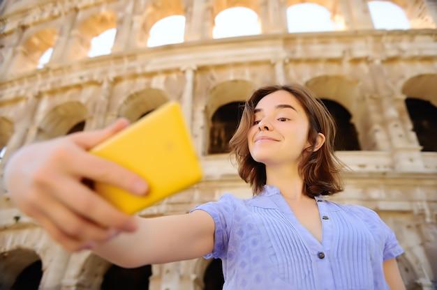 Jovem, femininas, viajante, fazendo, selfie, foto, ficar, colosseum, em, roma, itália Foto Premium