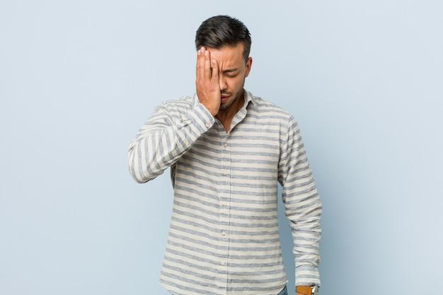 Jovem filipino bonito esquecendo algo, tapa na testa com a palma da mão e fechar os olhos. Foto Premium