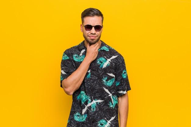 Jovem filipino vestindo roupas de verão sofre dor na garganta devido a um vírus ou infecção. Foto Premium