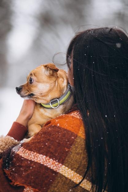 Jovem fora do parque com seu cachorrinho no inverno Foto gratuita