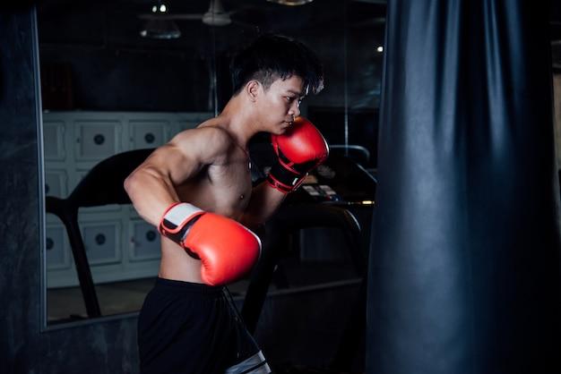 Jovem forte boxer de esportes homem fazer exercícios no ginásio, conceito saudável Foto gratuita