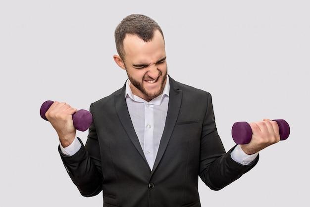 Jovem forte e bem constituído de terno fica e segura dois dumbells nas mãos. ele se exercita muito. Foto Premium