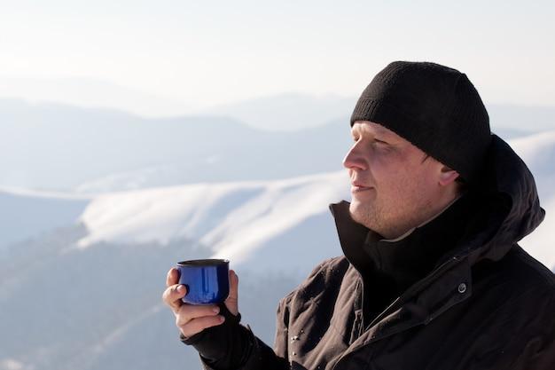 Jovem fotógrafo de homem sorridente em roupas de inverno, bebendo chá de garrafa térmica Foto Premium