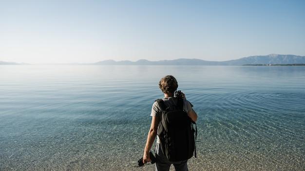 Jovem fotógrafo de pé à beira-mar, segurando a câmera e tripé Foto Premium