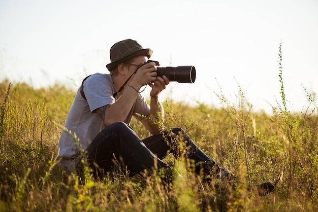 Jovem fotógrafo masculino no chapéu tirando foto, sentado no campo Foto gratuita