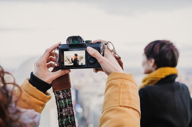 Jovem fotógrafo tirando uma foto de mulher bonita ao ar livre. fotografia, viagem Foto Premium