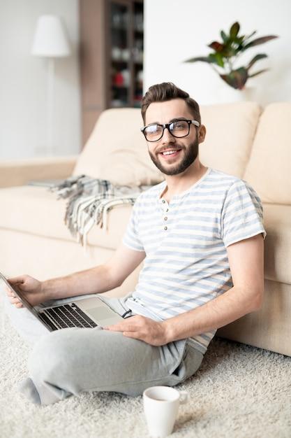 Jovem freelancer alegre de camiseta listrada e calça de moletom, sentado no chão e trabalhando na rede em casa Foto Premium