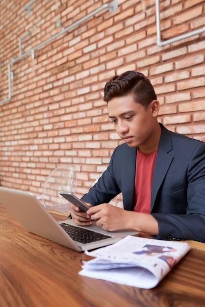 Jovem freelancer asiático sentado com laptop e verificação de smartphone Foto gratuita