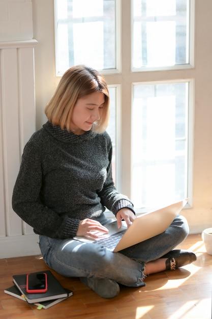Jovem freelancer profissional trabalhando em seu projeto enquanto está sentado perto das janelas Foto Premium
