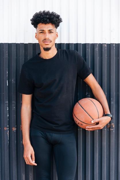 Jovem, fresco, posição homem, contra, parede, segurando, basquetebol Foto gratuita