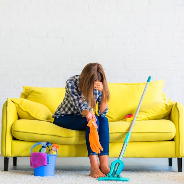 Jovem frustrada sentado no sofá com equipamentos de limpeza Foto gratuita