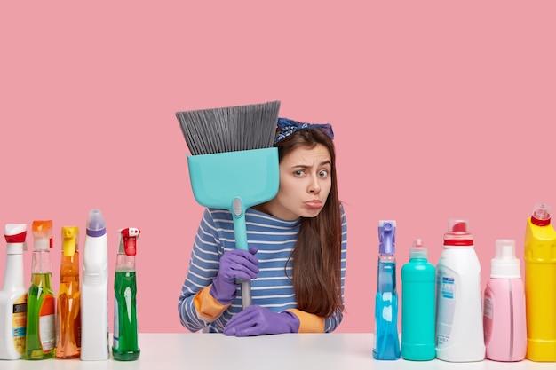 Jovem funcionário infeliz de serviço de limpeza segura a vassoura, usa várias substâncias de limpeza, não está pronto para começar a trabalhar, tem atitude negativa em relação ao trabalho Foto gratuita