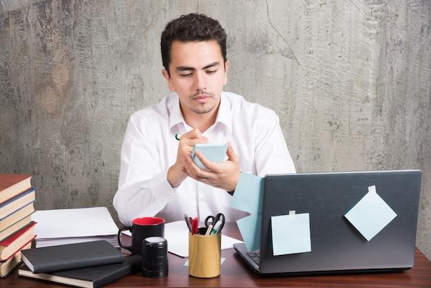 Jovem funcionário olhando para o telefone na mesa do escritório. Foto gratuita