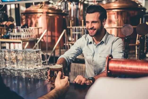 Jovem garçom está dando cerveja para clientes e sorrindo. Foto Premium