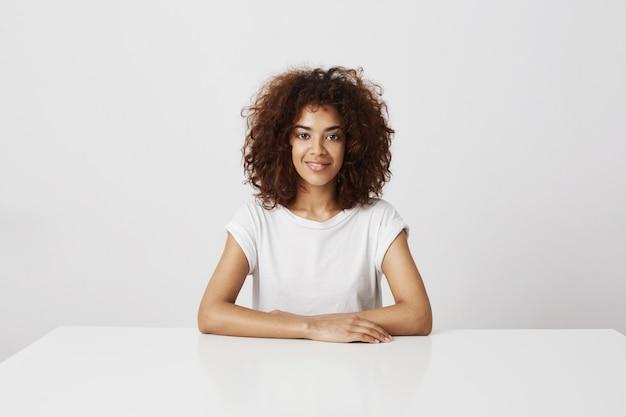 Jovem garota africana bonita em copos sorrindo sentado sobre parede branca Foto gratuita