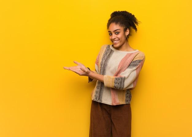 Jovem garota afro-americana negra com olhos azuis, segurando algo com as mãos Foto Premium