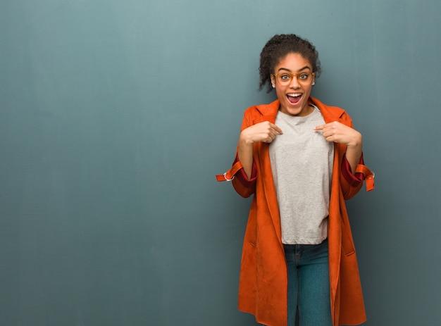 Jovem garota afro-americana negra com olhos azuis surpresa, sente-se bem-sucedida e próspera Foto Premium
