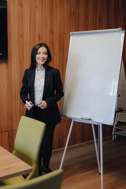 Jovem garota atraente emocional em roupas de estilo comercial, trabalhando com flipchart em um escritório ou audiência moderna Foto Premium