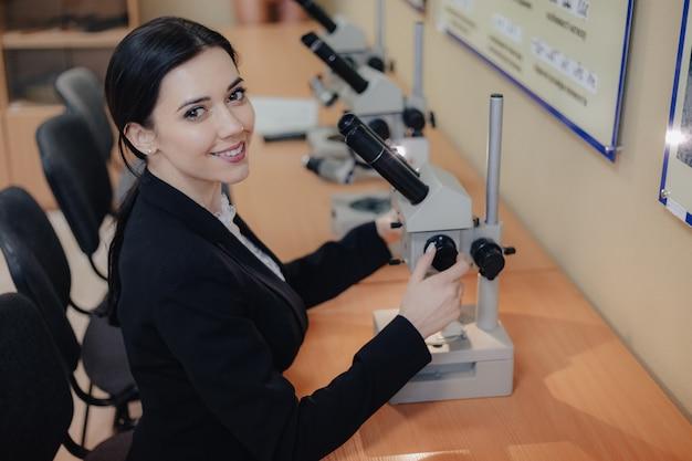 Jovem garota atraente emocional, sentado à mesa e trabalhando com um microscópio em um escritório ou audiência moderna Foto gratuita