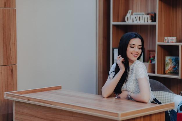 Jovem garota atraente emocional sentado em uma mesa Foto Premium