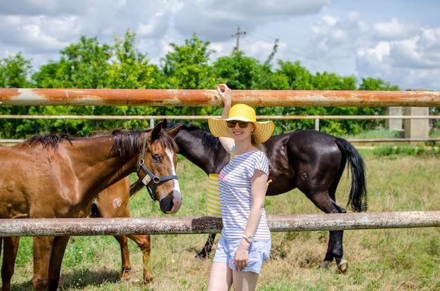 Jovem garota caucasiana em um chapéu amarelo e roupas de verão em pé perto do pasto com cavalos, sorrindo e olhando para a câmera. excursão à fazenda com animais. copiar spase Foto Premium