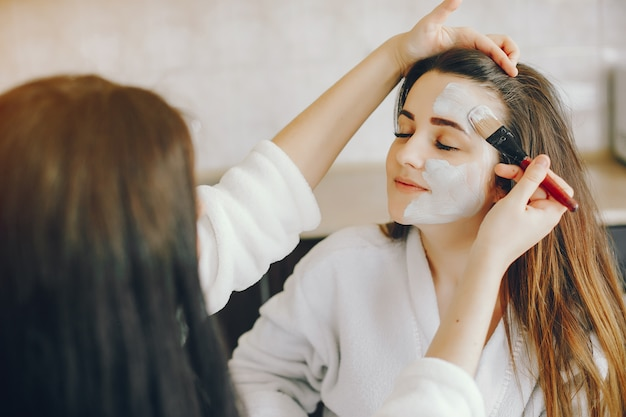 Jovem garota com belas mãos coloca uma máscara refrescante no rosto da namorada com um pincel Foto gratuita
