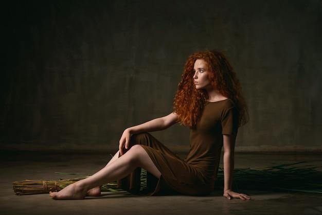 Jovem garota com cabelo ruivo cacheado senta-se na bengala seca em um vestido de cor cáqui Foto Premium