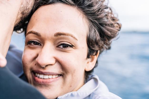 Jovem garota com cabelos cacheados, olhando para a frente enquanto ela abraça seu parceiro com o mar sem foco Foto gratuita