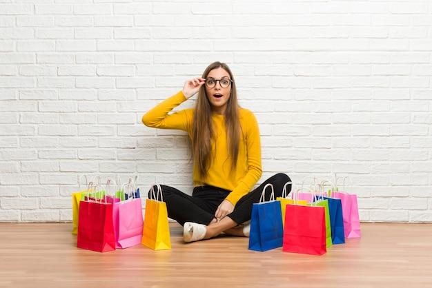 Jovem garota com muitos sacos de compras com óculos e surpreso Foto Premium
