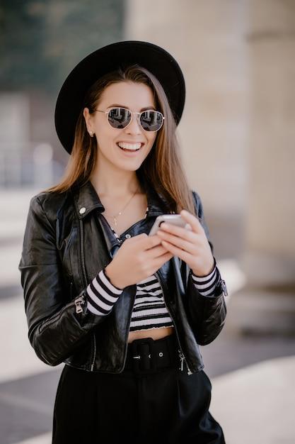 Jovem garota de cabelos castanhos em uma jaqueta de couro, chapéu preto no calçadão da cidade e joga no celular Foto gratuita