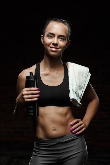 Jovem garota esportiva bonita sorrindo, posando, isolado na parede preta Foto gratuita