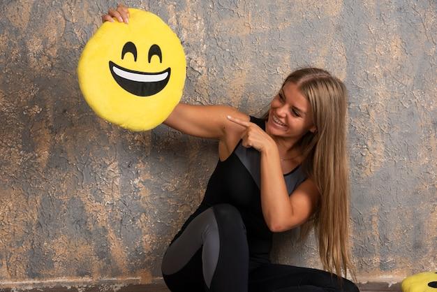 Jovem garota esportiva em trajes de esporte, segurando uma almofada de emoji sorridente e apontando para ela. Foto gratuita