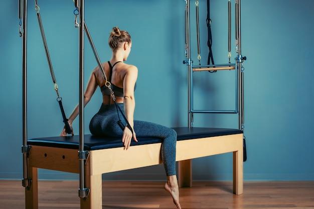 Jovem garota fazendo pilates exercícios com uma cama de reformador. instrutor magro bonito da aptidão no fundo cinzento do reformador, baixa chave, luz da arte. conceito de fitness Foto Premium