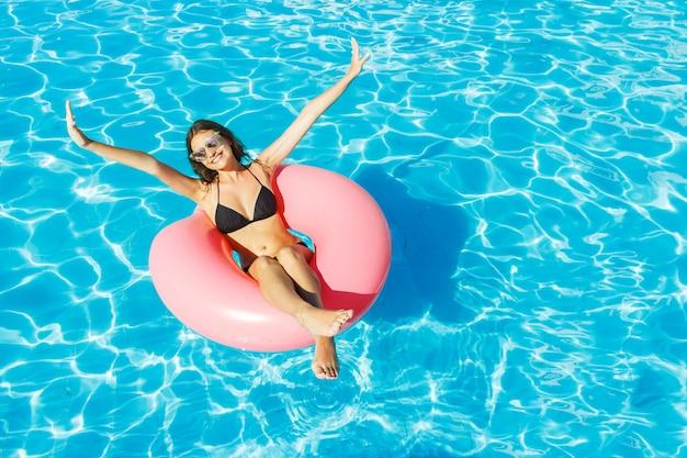Jovem garota feliz em biquíni está nadando na piscina com um círculo rosa Foto Premium